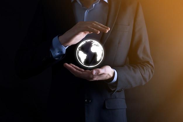 Biznesmen z ochronnym gestem postawa stojąca ręka trzyma ikonę ziemi