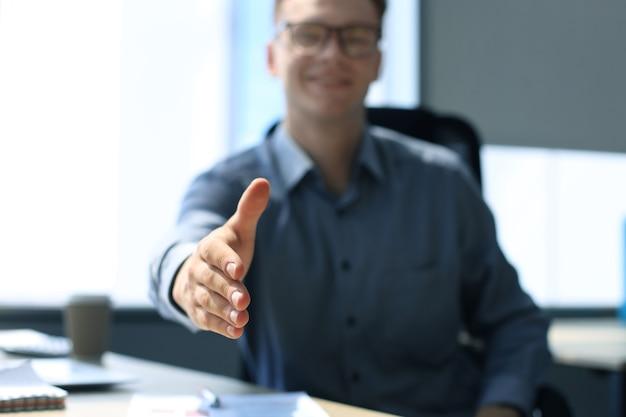 Biznesmen z otwartą dłonią gotowy do przypieczętowania transakcji w biurze.