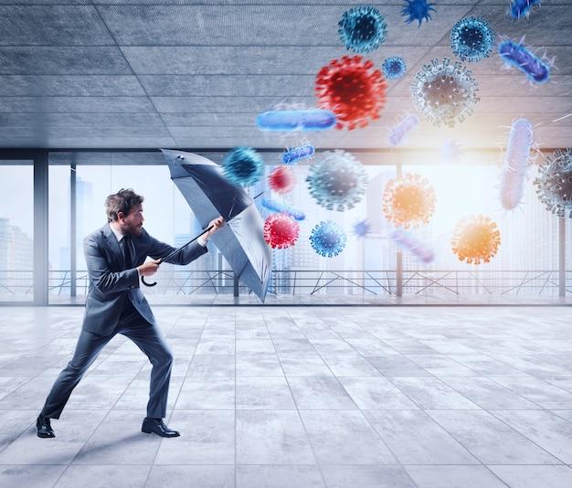 Biznesmen z parasolem zakrywa się przed bakteriami