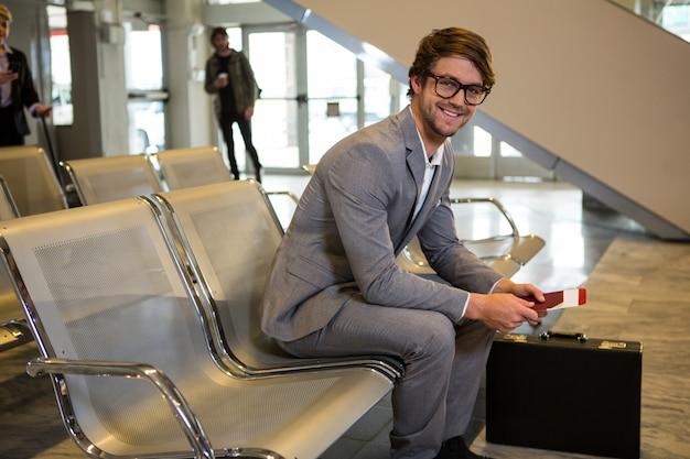 Biznesmen z paszportem, kartą pokładową i teczki siedzi w poczekalni