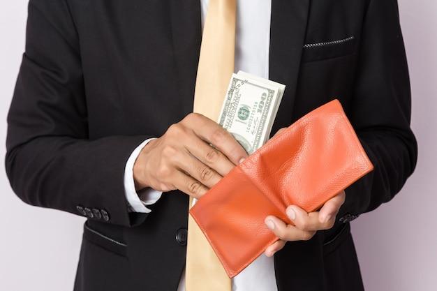 Biznesmen z pieniądze i pomarańczowy portfel w studiu. pomysł na biznes