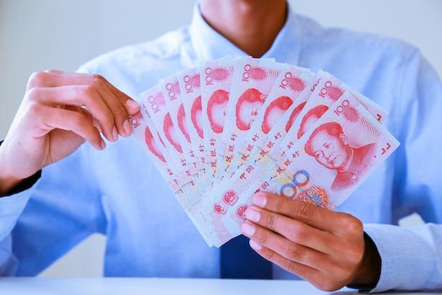 Biznesmen z pieniędzmi w ręku, yuan, inwestycje, sukces i zyskowne koncepcje biznesowe.