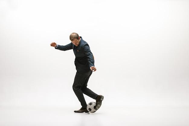 Biznesmen z piłką nożną w biurze. freestyle w piłce nożnej. pojęcie równowagi i zwinności w biznesie.