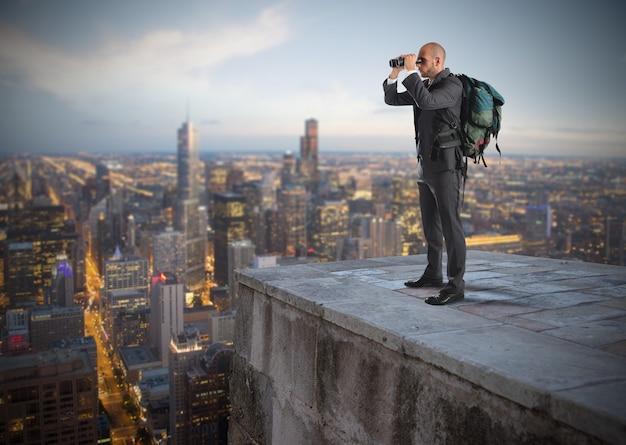 Biznesmen z plecakiem i lornetką oglądając z góry miasto