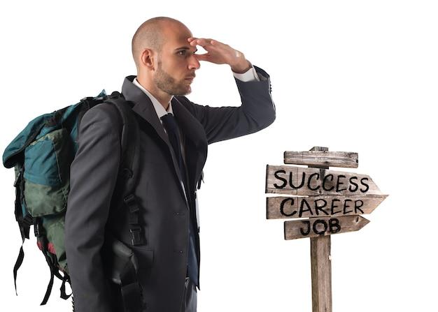 Biznesmen z plecakiem odkrywcy podąża za strzałkami kierunkowymi