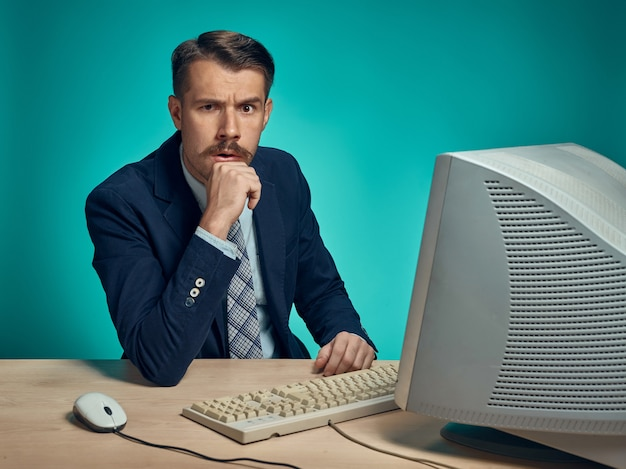 Biznesmen z podejrzanym spojrzeniem siedzi przy biurku przed komputerem