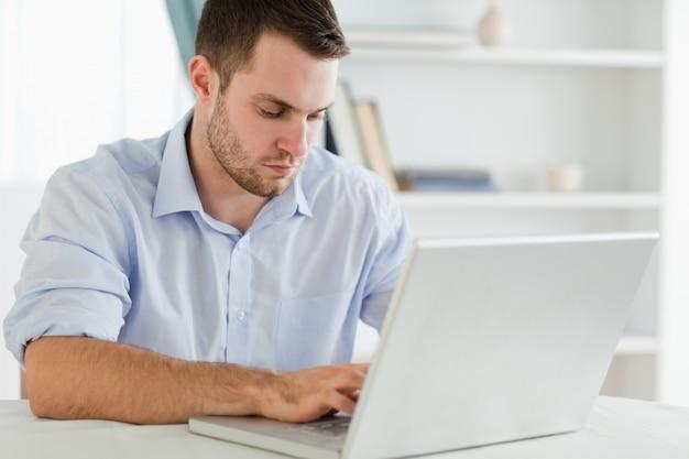 Biznesmen z podwiniętymi rękawami w swoim domu na laptopie