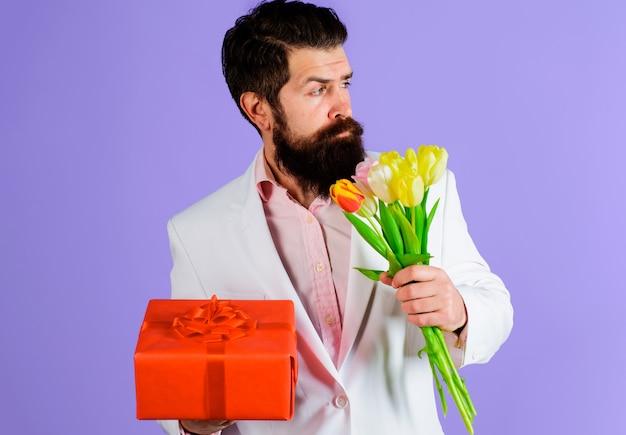 Biznesmen z prezentem i bukietem. romantyczny mężczyzna z tulipanami i teraźniejszością. walentynki, dzień kobiet, urodziny.