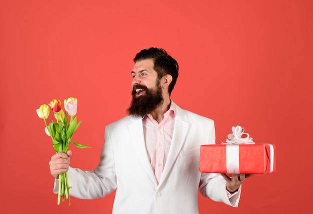 Biznesmen z prezentem i bukietem tulipanów na urodziny walentynki przystojny mężczyzna trzyma pudełko na prezent