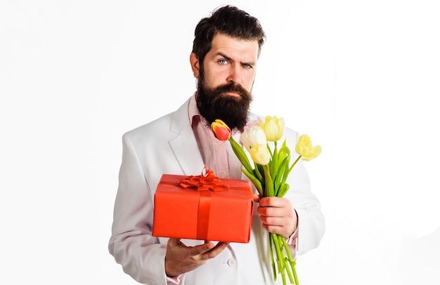 Biznesmen z prezentem i bukietem tulipanów. przystojny mężczyzna z teraźniejszością i kwiatami. urodziny, walentynki, dzień kobiet.