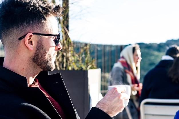 Biznesmen z przyciętą brodą i okularami przeciwsłonecznymi przy kawie na tarasie baru. zamazani ludzie w tle.