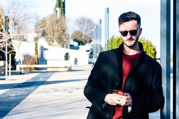 Biznesmen z przyciętą brodą za pomocą swojego telefonu komórkowego w przestrzeni miejskiej. sukienka z długim czarnym płaszczem i okularami przeciwsłonecznymi. oparty na kolumnie w mieście.