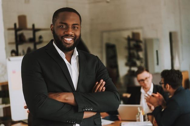 Biznesmen z rękami skrzyżowanymi uśmiecha się.