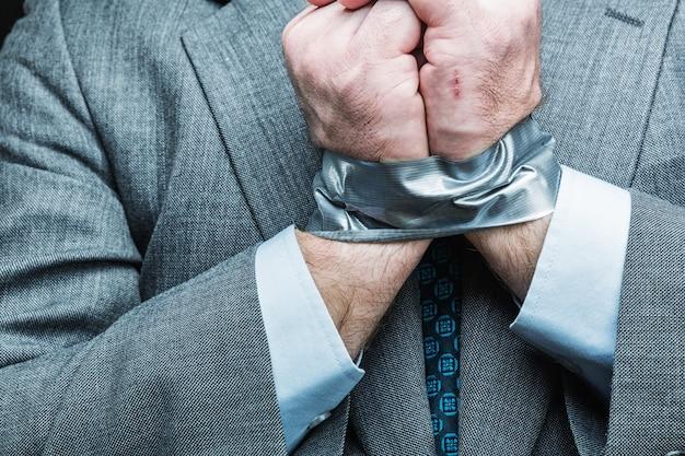 Biznesmen z rękami zakrytymi taśmą maskującą