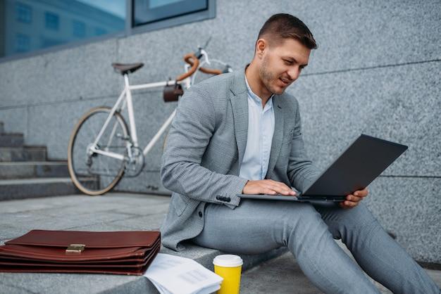 Biznesmen z rowerem i laptopem jedząc obiad w budynku biurowym w centrum miasta.
