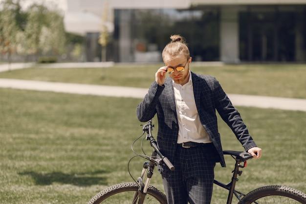 Biznesmen z rowerem w letnim mieście
