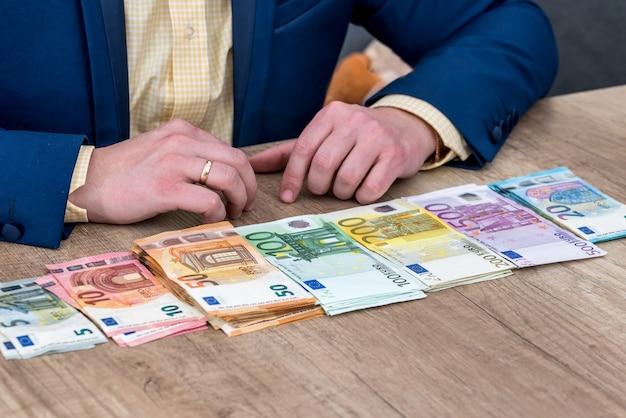 Biznesmen z rozproszonymi banknotami euro w rzędzie