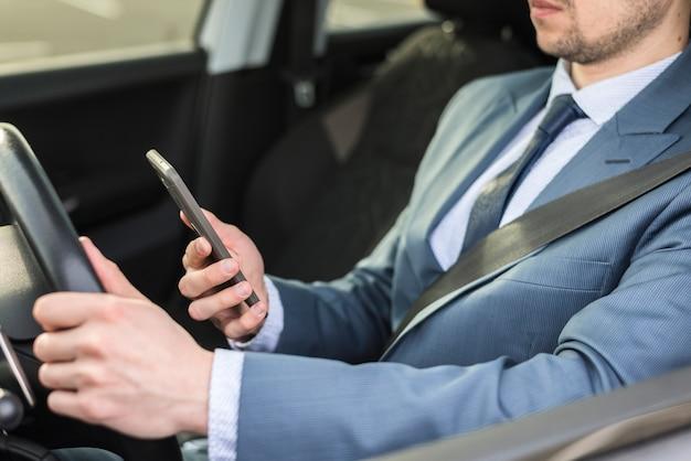 Biznesmen z smartphone w samochodzie