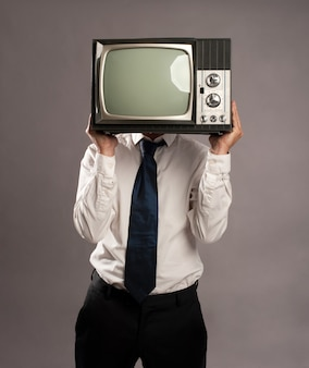 Biznesmen z starym telewizorem retro na głowie