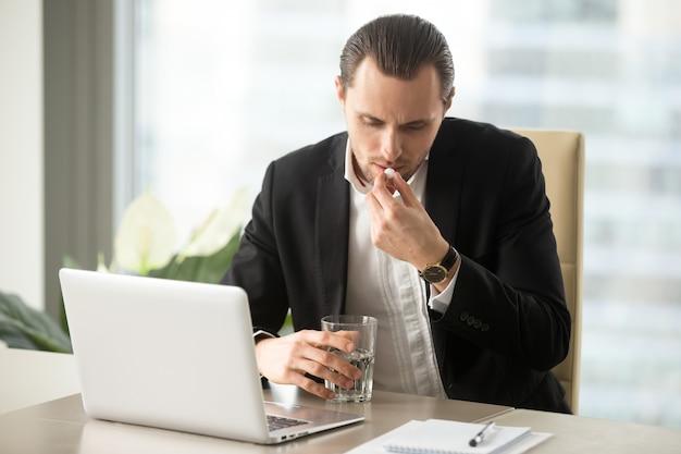 Biznesmen z szklanką wody bierze okrągłe pigułki