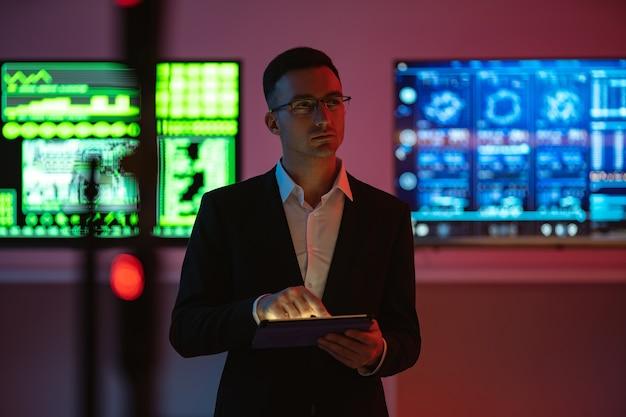 Biznesmen z tabletem stojącym na tle ekranów