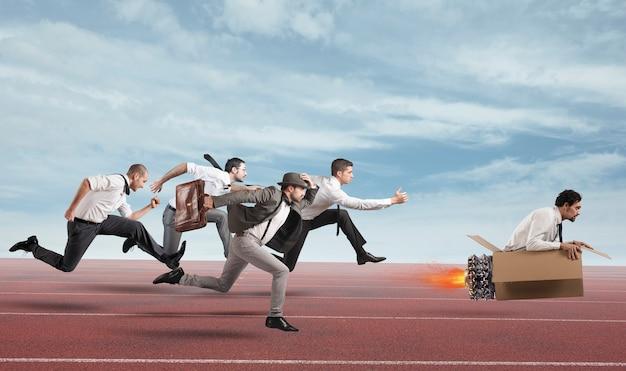 Biznesmen z tekturowym pociskiem pokonuje i wygrywa wyścig z przeciwnikami