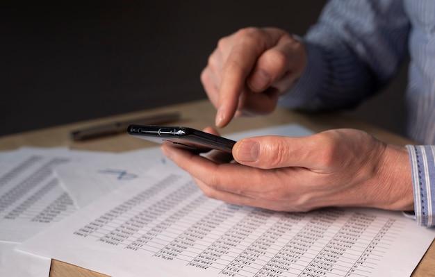 Biznesmen z telefonem komórkowym w ręce i dokumenty finansowe z numerami.