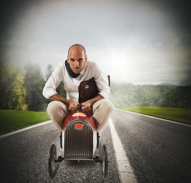 Biznesmen z torbą jedzie szybko mały samochód