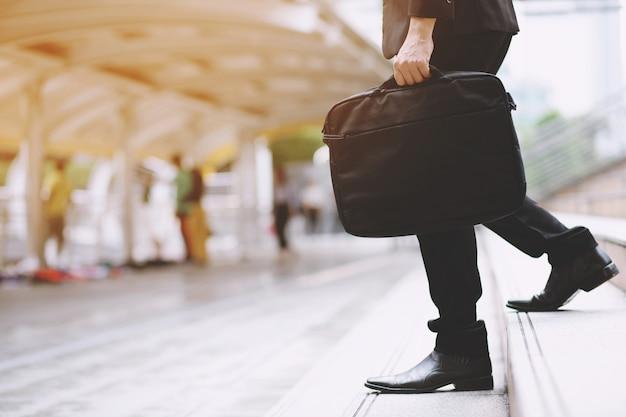 Biznesmen z torbą w ręku idąc schodami