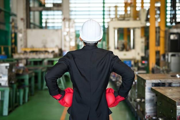 Biznesmen z tyłu w rękawiczkach i kasku gotowym do walki o przemysł fabryczny