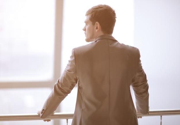Biznesmen z tyłu w stroju codziennym stojąc i myśląc w pobliżu okna biura