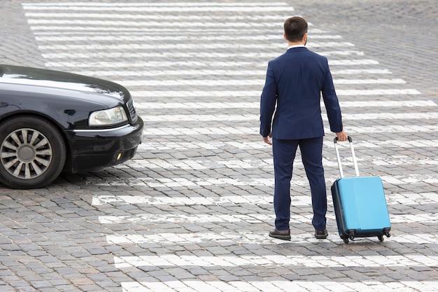 Biznesmen z walizką podróżną spaceruje po przejściu przez ulicę miasta