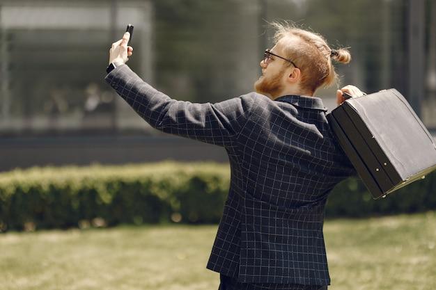 Biznesmen z walizką spaceru w letnim mieście