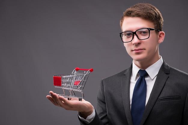 Biznesmen z wózek na zakupy na szarym tle