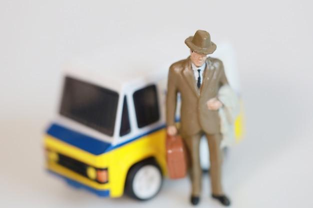Biznesmen z zabawkami stoi w pobliżu mini samochodu dostawczego do pracy z samochodem dostawczym na białym tle