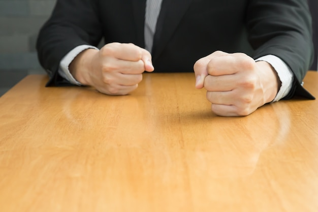 Biznesmen z zaciśniętą pięścią na biurku w biurze, pojęcie zły