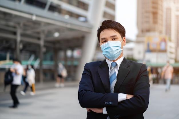 Biznesmen z założonymi rękami i nosząc maskę medyczną podczas pandemii koronawirusa w mieście