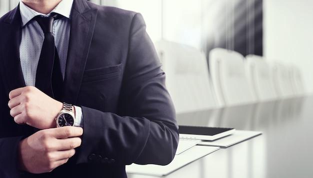 Biznesmen z zegarem i biurkiem konferencyjnym