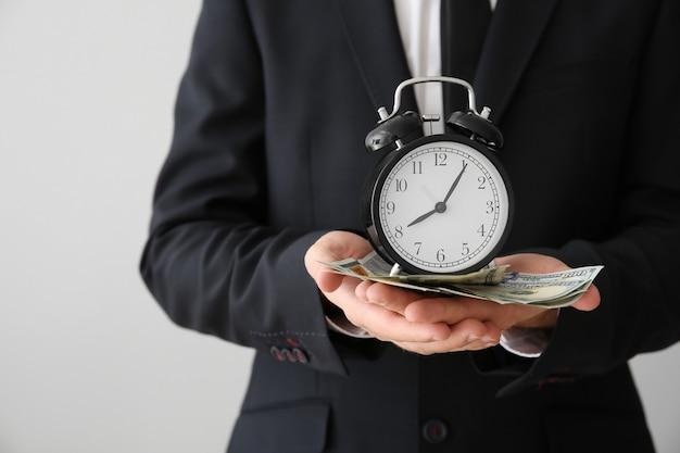 Biznesmen z zegarem i pieniędzmi na szaro