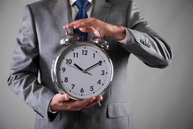 Biznesmen z zegarem w biznesowym pojęciu