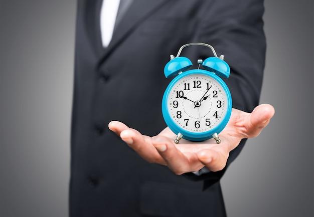 Biznesmen z zegarem w koncepcji czasu na tle