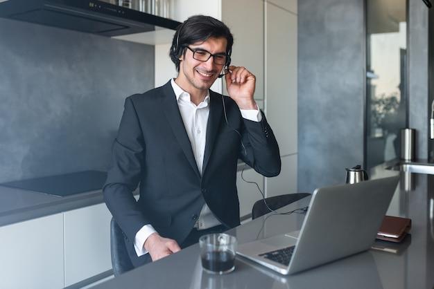 Biznesmen z zestawem słuchawkowym na wideokonferencji ze swojego komputera w domu