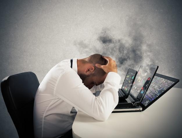 Biznesmen z zmartwioną miną z komputerami w dymie