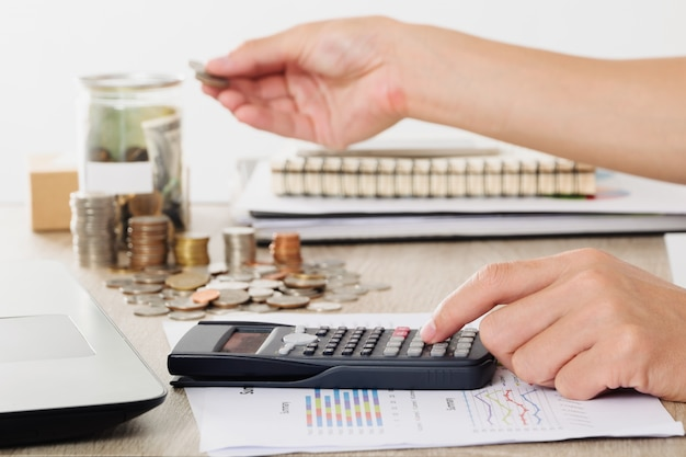 Biznesmen za pomoc? kalkulatora na biznes wykres, sprawozdanie finansowe z monetami i strony wprowadzenie monet pieni? dzy do banków oszcz? dzania pojemnika