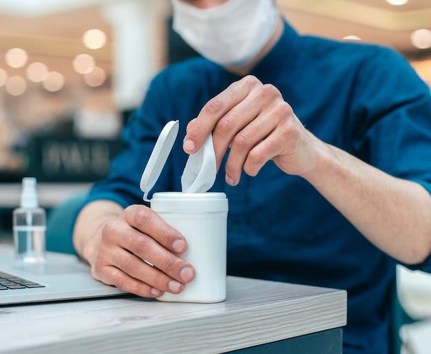 Biznesmen za pomocą chusteczek antyseptycznych siedzi przy stole