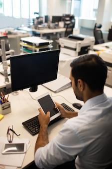 Biznesmen za pomocą cyfrowego tabletu, siedząc przy biurku w biurze
