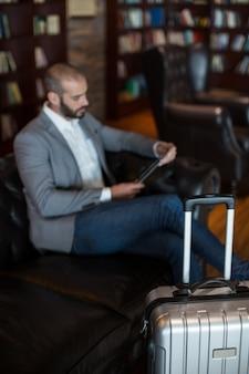 Biznesmen za pomocą cyfrowego tabletu w poczekalni