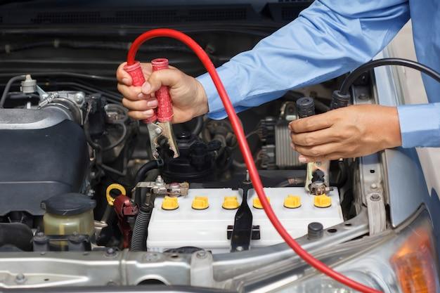 Biznesmen za pomocą kabli rozruchowych do uruchomienia samochodu na parkingu