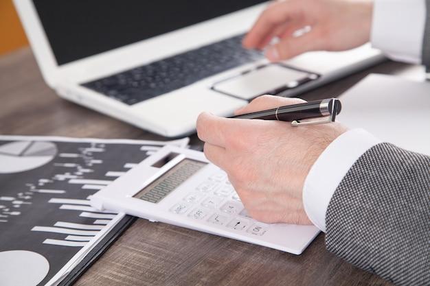 Biznesmen za pomocą kalkulatora do analizy planu marketingowego. rachunkowość biznesowa