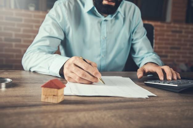 Biznesmen za pomocą kalkulatora i modelu domu w biurku